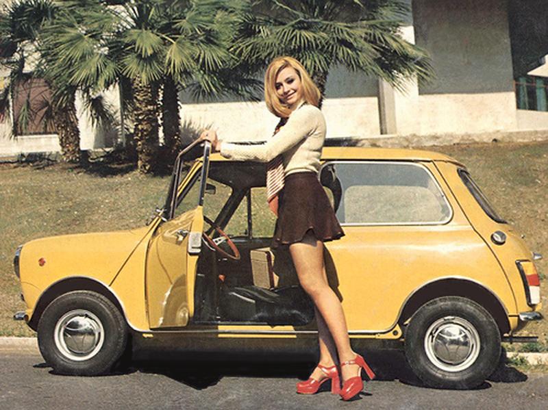 Raffaella Carrà posando de joven junto a un coche.